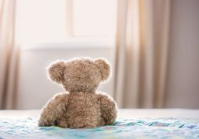 A teddy bear on a bed showing sleep tips for children with special needs - BedGuard